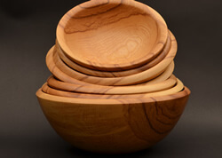 "Stack of ash salad bowls, featuring beautiful grain patterns and warm, honey-brown heartwood.  Largest is 13"" diameter, 5½"" height turned by Dennis Curtis."